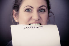 Stressed business woman biting contract Royalty Free Stock Photo