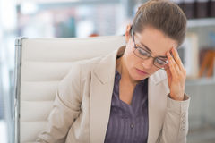 Stressed business woman with eyeglasses in office. Portrait of stressed business woman with eyeglasses in office Stock Photography