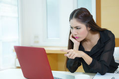 Stressed business woman is frustrated and point to screen. Stock Image