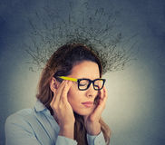 Stressed business woman having headache brain melting into lines question mark. Portrait stressed young business woman having headache with worried face Stock Photo