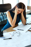 Stressed business woman at her working place. Business People Stock Photo