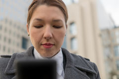 Stressed business woman holding cellphone in hands on the city. Street Royalty Free Stock Images