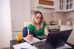 Stressed business woman at home working - planning budget and finances paying bills. Stressed young business woman at home working - planning budget and stock images