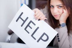 Stressed business woman imploring for help, holding a cardboard royalty free stock photo