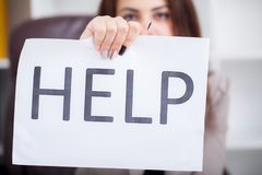 Stressed business woman imploring for help, holding a cardboard. With the message `Help`. Focus is on the cardboard Stock Images