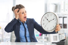 Stressed business woman looking on clock. In office Royalty Free Stock Photos