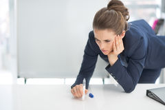 Stressed business woman near flipchart. In office Royalty Free Stock Photos