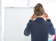 Stressed business woman near flipchart. rear view Stock Image