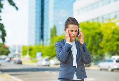 Stressed business woman in office district talking smartphone Royalty Free Stock Images