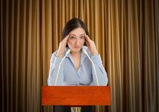 Stage fright to public speaking. Stressed business woman on the podium ready to address his audience Royalty Free Stock Photography