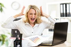 Stressed business woman screaming loudly working. Stressed business woman screaming loudly at laptop in office Royalty Free Stock Image