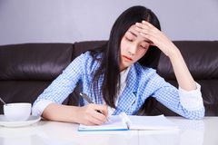 Stressed business woman sitting at her desk and writes a note on royalty free stock images