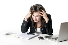 Stressed business woman. Sitting in office at desk, looking at laptop and holding his hands to his head Stock Photos