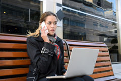 Stressed business woman talking on the phone with her laptop. Royalty Free Stock Photography
