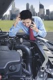 Stressed businessman asking for a mechanic help. Stressed Asian businessman using a mobile phone asking for a mechanic help to fix a car Royalty Free Stock Photo