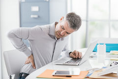Businessman with backache. Stressed businessman with backache, he is working at office desk and massaging his back Stock Photos