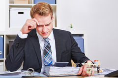 Stressed businessman with burnout. Stressed businessman sitting with burnout in his office royalty free stock photography