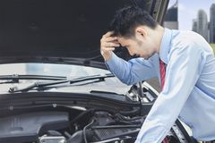 Confused businessman looking at car engine. Stressed businessman checks the car engine trying to find the solution to fix his car Stock Photos
