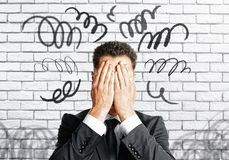 Stressed man covering face. Stressed businessman covering face on white brick wall background with scribble. Stress concept Royalty Free Stock Images