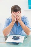 Stressed businessman covering his face at his desk Royalty Free Stock Image