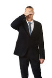 Stressed businessman covering his face Royalty Free Stock Photo