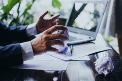 Stressed businessman in dark suit sitting at office desk full wi. Overload, overwork on business field, asked for ideas Royalty Free Stock Photo