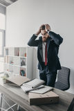 Stressed businessman with documents and folders standing at table in office Royalty Free Stock Photo