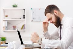 Stressed businessman working with laptop in modern white office. Stressed businessman in formal clothes thinking in modern white office. Job problems concept Stock Photo