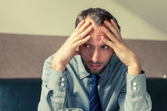 Stressed businessman getting a headache at home in the living ro Stock Photos
