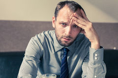 Stressed businessman getting a headache at home in the living ro. Om Royalty Free Stock Photo