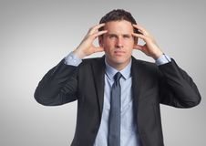 Stressed businessman with grey background Royalty Free Stock Photography