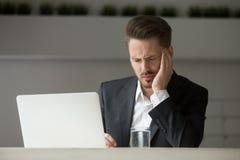 Stressed businessman having bad headache at work. Royalty Free Stock Photos