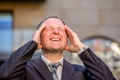 Stressed businessman having headache Stock Photo