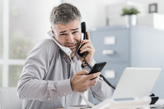 Stressed businessman having multiple calls Stock Images