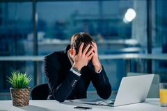 Stressed businessman having problems and headache at work. Sitting with laptop royalty free stock photo