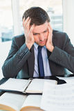 Stressed businessman with head in hands Royalty Free Stock Photos