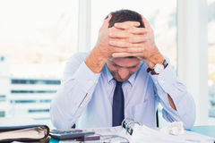 Stressed businessman with head in hands Stock Photography