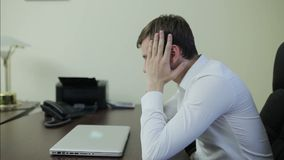 Stressed businessman with head in hands. At office stock video