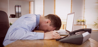 Stressed businessman with head on laptop Royalty Free Stock Image
