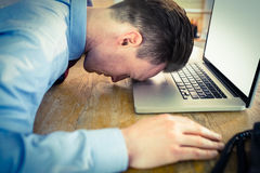 Stressed businessman with head on laptop Royalty Free Stock Images