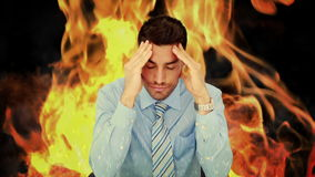 Stressed businessman with headache. On flaming background stock footage