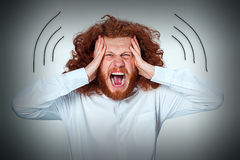 Stressed businessman with a headache. Hands of a man`s head is compressed Royalty Free Stock Image
