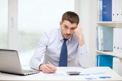 Stressed businessman with laptop and documents. Office, business, technology, finances and internet concept - stressed businessman with laptop computer and Stock Photo