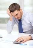 Stressed businessman with laptop and documents Stock Photo