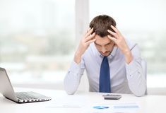 Stressed businessman with laptop and documents. Office, business, technology, finances and internet concept - stressed businessman with laptop computer and Stock Photos