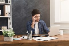 Stressed businessman with laptop in modern office. Young stressed, depressed and unhappy businessman with laptop in modern office interior. Handsome men at work Royalty Free Stock Images