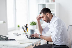 Stressed businessman with laptop at office. Business, people, deadline and technology concept - stressed businessman with laptop computer at office Royalty Free Stock Photos