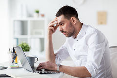Stressed businessman with laptop at office. Business, people, deadline and technology concept - stressed businessman with laptop computer at office Stock Photos