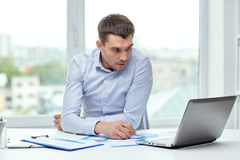 Stressed businessman with laptop at office. Business, people, deadline and technology concept - stressed businessman with laptop computer and papers at office Stock Image