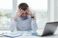 Stressed businessman with laptop at office. People, deadline and technology concept - stressed businessman with laptop computer and papers at office Royalty Free Stock Photos